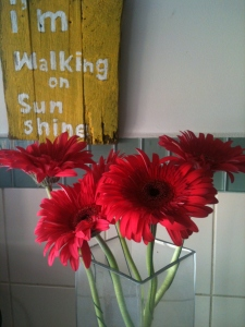 """Red gerbera flowers in a tall vase in front of home made """"I'm walking on sunshine"""" sign"""